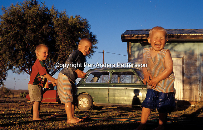 ORANIA, SOUTH AFRICA - SEPTEMBER 21: Unidentified children play with a water hose in a garden on September 21, 2003 in Klangelyk, a poor area of Orania, in the Northern Cape province, South Africa. The village was founded in 1991 and bought by descendants of Hendrik Verwoerd, the architect of Apartheid. It?s run as a private town only accepting whites. About 600 Afrikaners lives in the village where they celebrate their culture and keep traditions alive. They have chosen not to live in today?s South Africa; a country ran by a black government since 1994..(Photo: Per-Anders Pettersson/ iAfrika Photos......