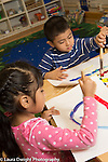 Education Preschool 4 year olds art activity painting boy and girl at work girl using right hand to hold brush and boy using left hand