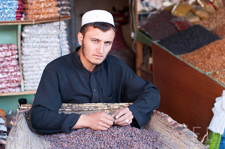 Portrait of an Afghan man selling dried nuts and spices in Kabul Bazar