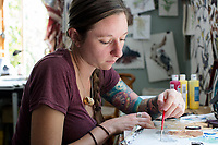 """Artist and illustrator Jada Fitch works on a small portrait of a Black-capped Chickadee in her living room, which doubles as her art studio, in Portland, Maine, USA, on Fri., July 28, 2017. Fitch uses bird identification books as inspiration for her portraits. Here, she uses the second edition of """"Sibley Birds East"""" as a guide. The portraits are a couple inches tall and are later placed in her """"Home Tweet Home"""" birdhouses. The birdhouses look like living rooms with small portraits of birds hung on the walls. The birdhouses sell out within minutes on her Etsy store."""