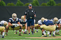 Head coach Brian Kelly watches stretching.