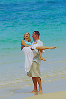 Couple playing on white sand beach on their honeymoon in Hawaii