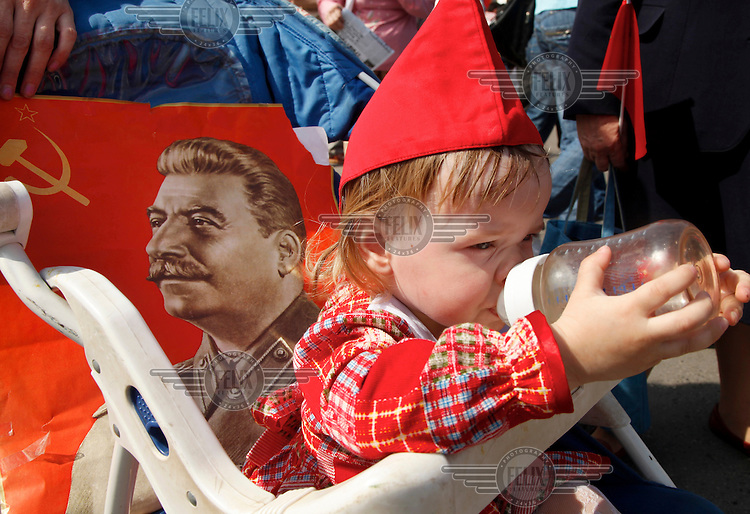 A child drinks milk during a communist march in central Moscow on Victory Day with portraits of former Soviet dictator Joseph Stalin.