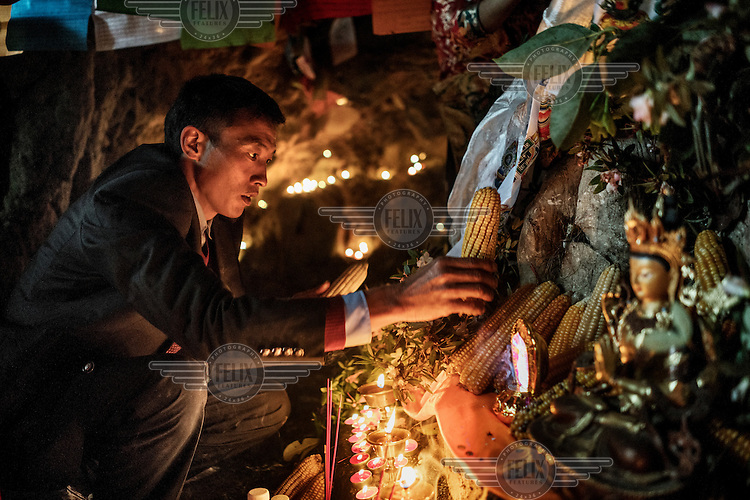 Local Nu, Lisu and Tibetan people celebrate the Fairy Festival and arrival of spring by leaving offerings of maize at a Tibetan Buddhist altar in a sacred cave.