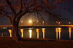 Idaho, South Central, Burley. A full moon and street lights on a bridge reflect in the Snake River at night.