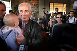 Shimon Peres, no. 2 at the Israeli Kadima party, holds a baby during an election campaign walk at the docks of Tel Aviv.<br /> March 17th, 2006 (Photo by Ahikam Seri).