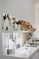 Utensils and kitchenware in a white modern kitchen with shelving above a stainless steel sink