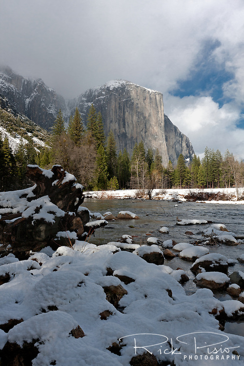 Snow lines the Merced River while clouds rest on  El Capitan in Yosemite National Park.