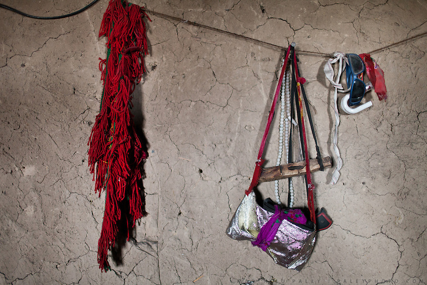 A shiny bag and some woolen red threads hanging on a mud wall. Campment of Tash Seri...Trekking with yak caravan through the Little Pamir where the Afghan Kyrgyz community live all year, on the borders of China, Tajikistan and Pakistan.
