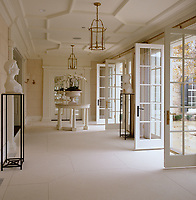 In the garden room a geometric pattern on the ceiling is echoed in the limestone floor and a series of elegant French windows opens out onto a terrace