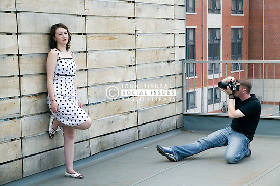Woman modelling for a photo shoot on a roof top with a photographer,
