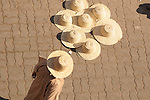 A man wearing a straw hat walks by straw hats for sell on the streets in Marrakesh, Morocco.