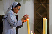 "A nurse candles a light as she attends a mass to commemorate the saint Laura of Saint Catherine of Siena known as ""Madre Laura"" at her mausoleum in Jerico, Colombia. May 12, 2013. Photo by Freddy Builes / VIEWpress."