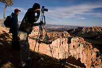 """Kat Cho, left, and Shen Chiu, of Sydney, Australia, make panoramic photos of Bryce Canyon National Park as the sun sets on its distinctive limestone """"hoodoos."""""""