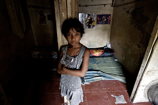 7 year-old Laxmi stands in front of the room she shares with her mother, Sangita, in a brothel on Hanuman Galli.