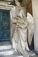 Picture and image of the stone sculpture of a mouyring widow and two children sitting by the doors of the tomb with an angel. The Patrone tomb sculpted by S Varni 1976. Section D, no 23, The monumental tombs of the Staglieno Monumental Cemetery, Genoa, Italy