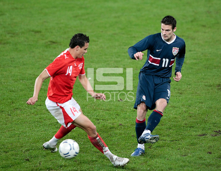 USA defender (11) Heath Pearce and Switzerland midfielder (14) David Degen. The United States Men's National Team (USA) defeated Switzerland (SUI) 1-0 during an international friendly at St. Jakob Park, Basel, Switzerland, on October 17, 2007.