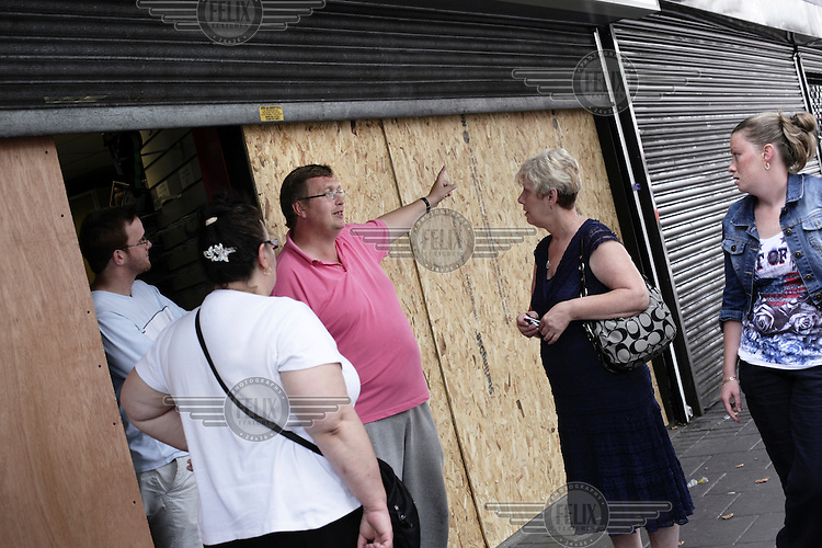 Graham Francis and David Cocks talk with other local residents about the rioting and looting that took place in the area in August 2011. TD Sports shop, on the Walworth Road, London, was subject to looting during the disturbances.