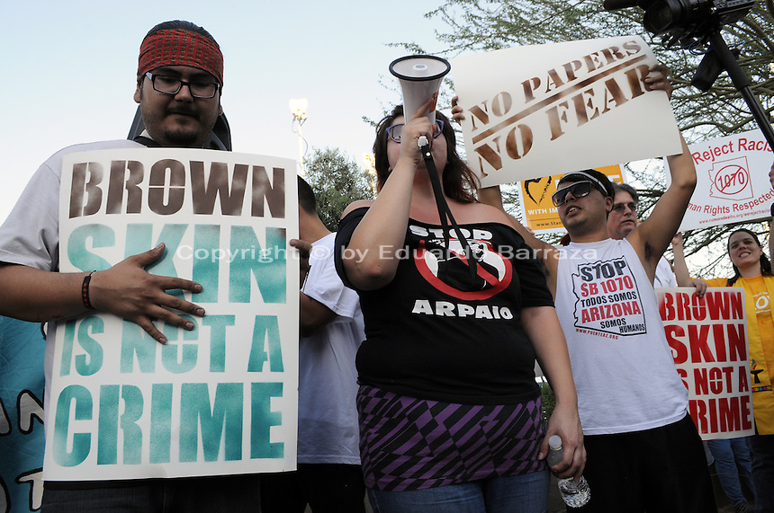 "Phoenix, Arizona. June 25, 2012 - Puente Arizona activists Orlando Arenas (left) and Erika Ovalle (with bullhorn) lead demonstrators with protest's chants like ""Arrest Arpaio, not the people."" Arenas was arrested by Sheriff Arpaio's deputies in 2009 for protesting at a county jail.  Immigrant rights groups protested the United States Supreme Court ruling on Arizona law for upholding SB 1070's provision that will allow police to demand papers if there's reasonable suspicion that a person may be illegally in the country. Photo by Eduardo Barraza © 2012"