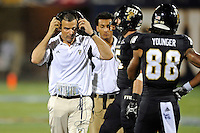 24 September 2011:  FIU Football Head Coach Mario Cristobal puts his headsets back on during a timeout in the third quarter as the University of Louisiana-Lafayette Ragin Cajuns defeated the FIU Golden Panthers, 36-31, at FIU Stadium in Miami, Florida.