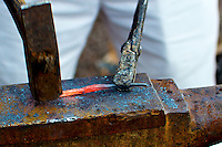 Blacksmith striking a red hot viking nail on an anvil