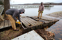 NWA Democrat-Gazette/DAVID GOTTSCHALK Nathan Albertson (left), grounds maintenance worker with the city of Fayetteville Parks and Recreation Department, cuts Monday, December 3, 2018, a steel brace from an old in the marina at Lake Fayetteville. The old dock is being replaced with a new 64 foot aluminum and composite decking dock. The project was made possible through a $8,000 Rotary Club donation, $5,000 from the Rowing Club of Northwest Arkansas and $25,000 in parkland dedication fees. The Fayetteville Parks and Recreation Advisory Board on Monday considered adjusting the one-time fee the city charges to developers of new properties.