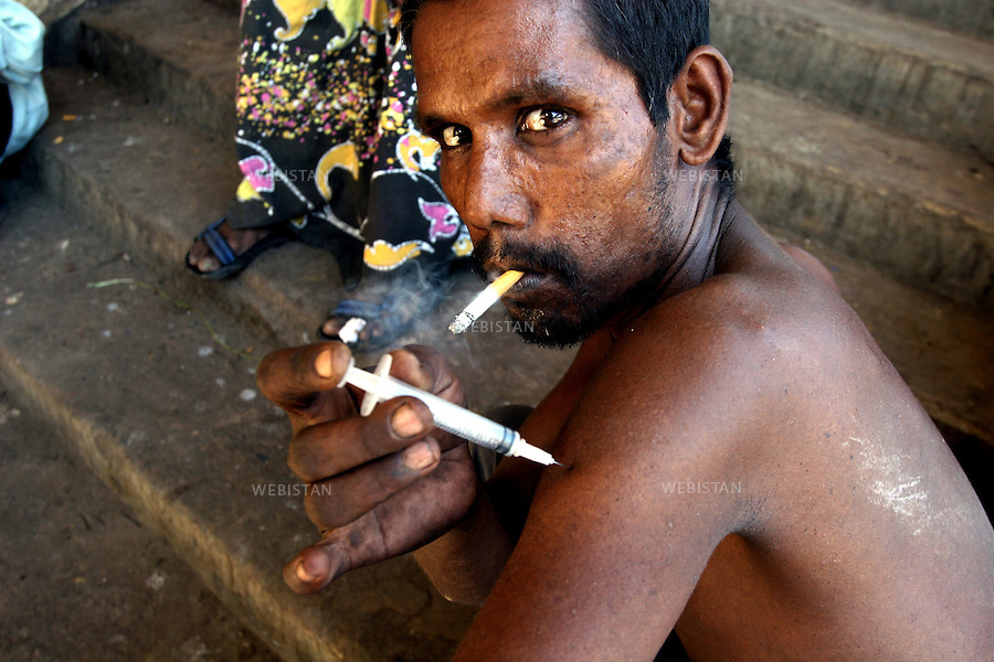 2005. Bangladesh, Dhaka. A man injects himself drug in the arm while smoking...2005. Bangladesh, Dhaka. Un homme s'injecte de la drogue dans le bras tout en fumant..