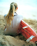 USA, Hawaii, Oahu, a young woman surfer sits on the beach and watches the waves at Pipeline, The North Shore