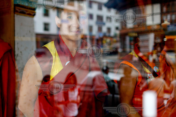 Monks seen through a glass window with the street scene reflected.