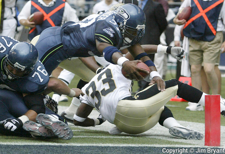 Seahawks' running back Shaun Alexander dives past Saint's cornerback Ashley Ambrose and into the end zone to score his second touchdown of the first half half on Sunday, Sept. 7, 2003 at Seahawks' Stadium. Jim Bryant Photo