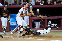 Catcher Grayson Greiner (21) of the South Carolina Gamecocks receives the ball too late to prevent LaMonte Wade (6) of the Maryland Terrapins from scoring in an NCAA Division I Baseball Regional Tournament game on Sunday, June 1, 2014, at Carolina Stadium in Columbia, South Carolina. Maryland won, 10-1, to win the tournament. (Tom Priddy/Four Seam Images)