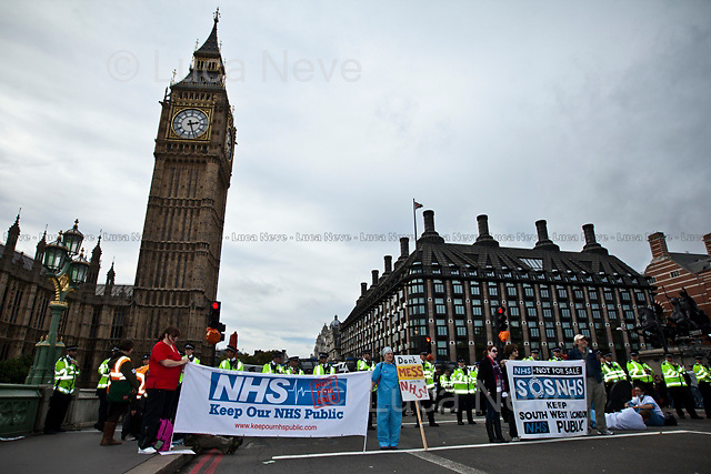 London, 09/10/2011. UK Uncut organised a peaceful occupation of Westminster Bridge to protest against the proposed reform of the NHS (National Health Service). Hundreds of people gathered since the morning on the iconic London bridge that connects the Houses of Parliament on one side with the major Guys and St Thomas Hospital on the other. Protestors said NO to the privatisation of UK hospitals and health services. In the afternoon a group of protesters tried to reach Parliament Square (which had been prohibited for the entire event) via Lambeth Bridge but police officers kettled them at the north side, and detained them there for an hour.