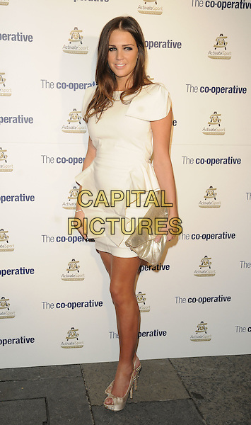 DANIELLE LLOYD .Activate Sport Foundation Launch Dinner - outside arrivals, Banqueting House, Whitehall Place, London, England, UK, October 31st 2010..full length white cream dress ruffle clutch bag gold peep toe shoes platform shoulder pads peplum .CAP/CAN.©Can Nguyen/Capital Pictures.