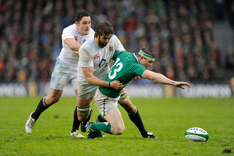Brian O'Driscoll of Ireland attempts to mop up a loose ball as he is tackled by Geoff Parling (centre) and Brad Barritt of England during the RBS 6 Nations match between Ireland and England at the Aviva Stadium, Dublin on Sunday 10 February 2013 (Photo by Rob Munro)