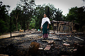 One of the victims of ethnic violence, Ronsomo Langthasa poses in front of her burnt house in Jorai village. Ethnic clashes are regularly taking place between Zeme Nagas and the Dimasa tribe in North Cachar Hills in Assam, India. On 8th May 200, suspected Zeme Naga groups attacked a Dimasa village and burnt down 10 out of 13 houses. In this act of violence, they spared the school and the community centre, where most of the families are taking shelter.
