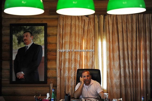 Ibrahim Ibrahimov, an Azerbaijani oligarch and billionaire, talks on his cell phone during a meeting at the on-site office of the Khazar Islands project underneath a portrait of Azerbaijani President Ilham Aliyev near Sahil, Azerbaijan on July 18, 2012.  The brainchild of Ibrahimov, the artificial Khazar Islands project just southwest of the Azerbaijani capital Baku is being built at a projected cost of $100 billion with an anticipated 800,000 housing units.