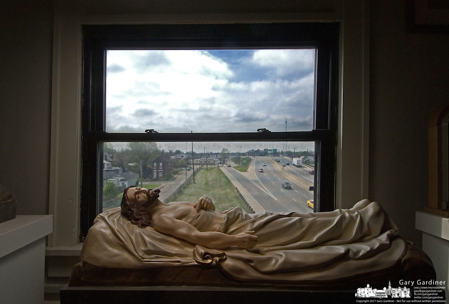 Corpus of Christ sits at a window in a Catholic relic museum overlooking a city freeway.<br />
