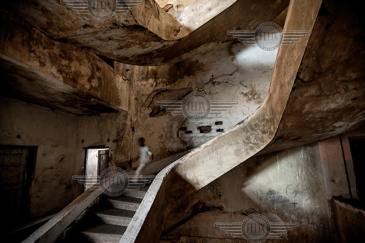 A boy  walks down a stairway inside the former Grand Hotel building. Once a luxury destination for the wealthy and the continent's biggest hotel, the building is now a concrete shell and home to about 6,000 squatters. Those unable to occupy one of the rooms sleep in the corridors, basements and even on the roof of the building.