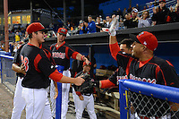 Batavia Muckdogs pitcher Ryan Newell (38) is greeted by Carlos Lopez (hidden), Scott Carcaise and Jose Ceballos after going 8 hitless innings giving up a bloop single in the ninth during a game against the Aberdeen Ironbirds on August 10, 2013 at Dwyer Stadium in Batavia, New York.  Batavia defeated Aberdeen 1-0.  (Mike Janes/Four Seam Images)