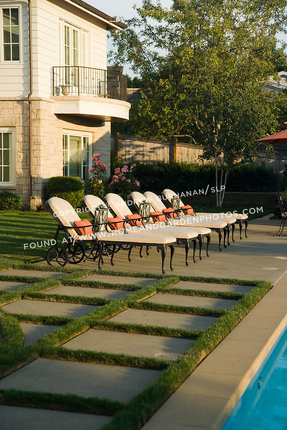 An peaceful, early summer evening view of a beautifully manicured, poolside landscape featuring geometrically patterned concrete pavers intersperced with lush green grass lawn, and matching chaise lounge chairs aligned along the pool's edge in this Northwest summer scene in a suburban community east of Seattle.