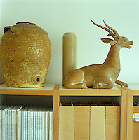 Amongst the objects on the living room bookshelves is an antique olive oil jar and a ceramic antelope acquired in New York