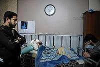 Syria, Deir az-Zor, 2013/03/21..A man suffers shrapnel injuries after the main street was shelled this day. Al-Noor hospital is  the largest hospital in town to treat injured or register deads from fightings or shelling in the embattled town at the banks of Eurphrates river. Conditions are poor and all staff works since two years almost non-stop. Even skilled teenager are needed to maintain proceedings as Wissam fullfills his job for his age in an incredible manner..Syrie, Deir ez-Zor, 21/03/2013.Un homme souffre de blessures causées par des éclats d'obus lors du bombardement de la rue principale. Al-Noor est le plus grand hôpital de la ville pour soigner les blessés ou enregistrer les  morts aux combats ou lors de bombardements dans la ville assiégée. Les conditions sont mauvaises et l'ensemble du personnel travaille depuis deux ans presque non-stop. Même l'emploi d'adolescents est nécessaire pour maintenir les services ouverts à l'image de Wissam qui fait son travail d'une manière incroyable pour un garçon de cet âge..Photo: Timo Vogt / Est&Ost Photography.