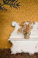 An Italian 18th century garden bench has been placed against one of the yellow-painted brick walls in the orangery