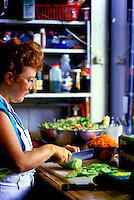 A woman wearing an apron cuts up vegetables in her kitchen.