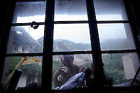 Sun Ayue, one of very few residents of the abandoned fishing village of Hautouwan on the island of Shengshan is seen from inside the room where he lives July 25, 2015. A 59 year old former fisherman Sun Ayue, who never leaves village except for occasional game of mahjong in town across the hill, lives alone in a house with no running water and electricity. Every day hundreds of tourists make their way on narrow footpaths between some of 500 houses covered by bewildered vegetation at Hautouwan, once home to over 2000 fishermen. The fishing village, a part of the Shengsi archipelago east of Shanghai was abandoned in early 90s and now only less than a half dozen people live there. REUTERS\Damir Sagolj