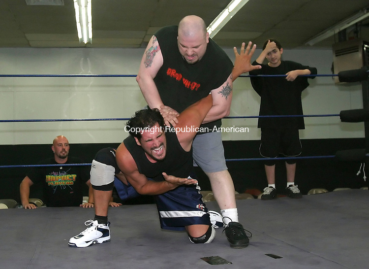 WATERBURY, CT 7/2/07- 070207BZ08-  Pat Gunner, on mat, and Bull Dredd, standing, wrestle during practice at The Proving Grounds Wrestling School on East Main Street in Waterbury. The school is part of Defiant Pro Wrestling.  In the background are Justin Credible, left, and Jonathan Ramirez, right.<br /> Jamison C. Bazinet Republican-American