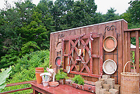 Garden potting bench and containers, pig statue ornament, baskets, hanging antique tools, pots, asparagus fern growing in old drawer, for charming place outdoors for gardening chores
