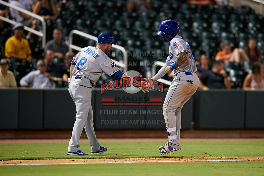 Tennessee Smokies right fielder Eddy Martinez (20) is congratulated by manager Mark Johnson (8) as he rounds third base after hitting a home run in the top of the seventh inning during a game against the Birmingham Barons on August 16, 2018 at Regions FIeld in Birmingham, Alabama.  Tennessee defeated Birmingham 11-1.  (Mike Janes/Four Seam Images)