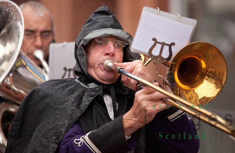 A wet Guid Nychburris 2012 in Dumfries Visually impaired rain on glasses of musician trombone player in brass band trying to read music in rain.