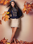 Smiling teenage girl artistic fall fashion photo with red autumn leaves